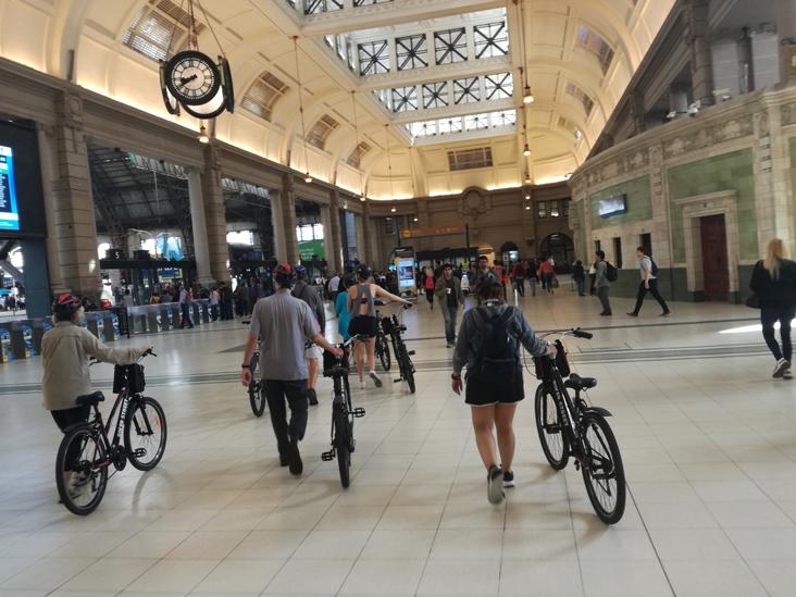 Walking with bikes at Retiro Train Station during bike & kayak tour to Tigre
