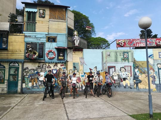 taking pictures in a mural in La Boca during a bike tour